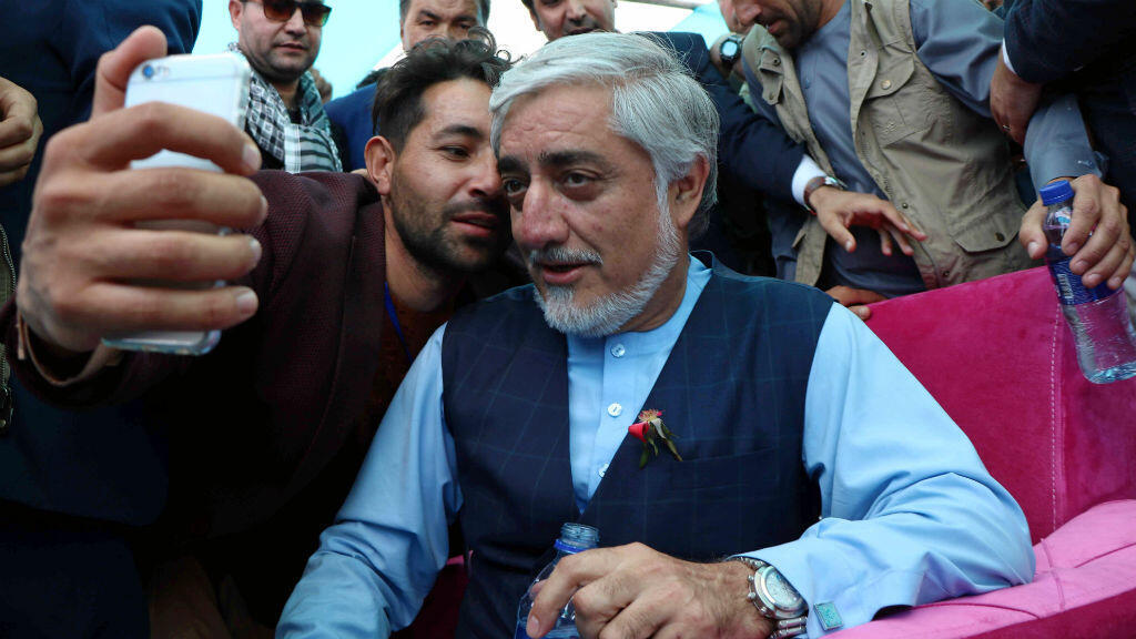 El candidato presidencial de Afganistán, Abdullah Abdullah, se toma una selfie con un partidario durante la campaña electoral en la provincia de Herat, Afganistán, el 24 de septiembre de 2019.
