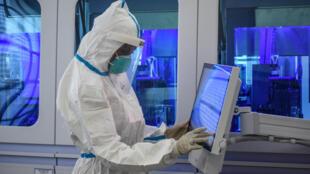 Un técnico maneja a través de una pantalla muestras para realizar la prueba del coronavirus, el 14 de mayo de 2020 en el laboratorio del Instituto de Investigación Médica de Kenia situado en Busia, ciudad al oeste del país fronteriza con Uganda
