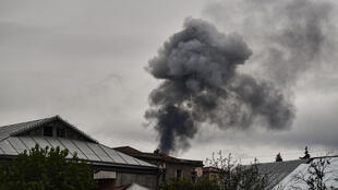Smoke rises behind houses after shelling in the breakaway Nagorno-Karabakh region's main city of Stepanakert on October 7, 2020, during the ongoing fighting between Armenia and Azerbaijan over the disputed region.