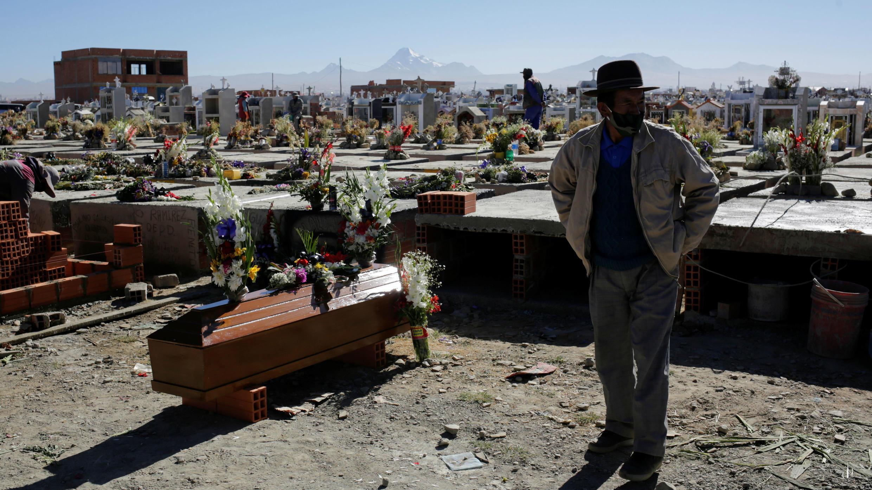 Un hombre se encuentra junto al ataúd de su pariente en el cementerio de Mercedario, en medio del brote de coronavirus, en El Alto, a las afueras de La Paz, Bolivia, el 21 de julio de 2020.