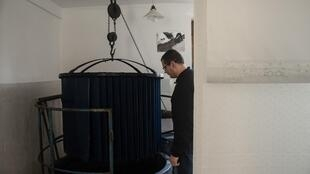 Czech craftsman Jiri Danzinger dips a wax printed cotton textile in a tub of water dyed indigo blue