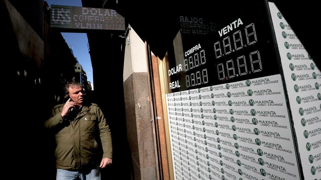 n transeúnte camina frente a una pantalla que informan el valor de monedas extranjeras, encabezadas por el dólar, respecto al peso argentino este martes 13 de agosto, en Buenos Aires (Argentina).