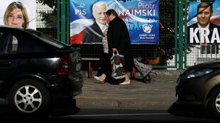 A woman walks in front of election banners in Warsaw, Poland, on October 12, 2019