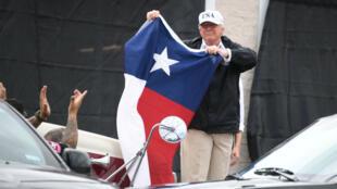 Le président Donald Trump agitant le drapeau bleu, blanc et rouge du Texas, mardi 29 août à Corpus Christi, au Texas.