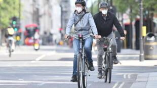 شخصان يرتديان قناعين واقيين يركبان دراجتين هوائيتين في لندن في 2 أيار/مايو 2020