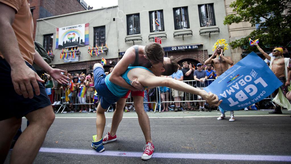 Imagen de archivo. Dos participantes en una marcha del Orgullo Gay se besan frente al Stonewall Inn. Nueva York, EE. UU., el 24 de junio de 2012.