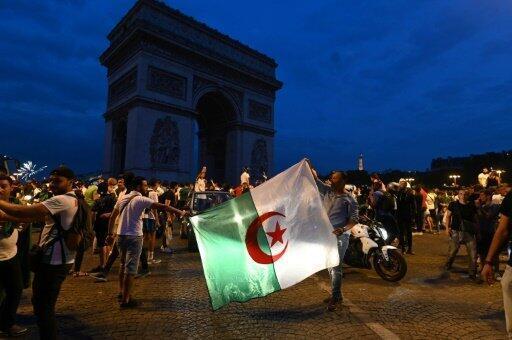 مشجعون للمنتخب الجزائري بالقرب من قوس النصر في باريس يحتفلون بفوز المتنخب في مباريات ربع النهائي لكأس الأمم الأفريقية في 11 تموز/يوليو 2019