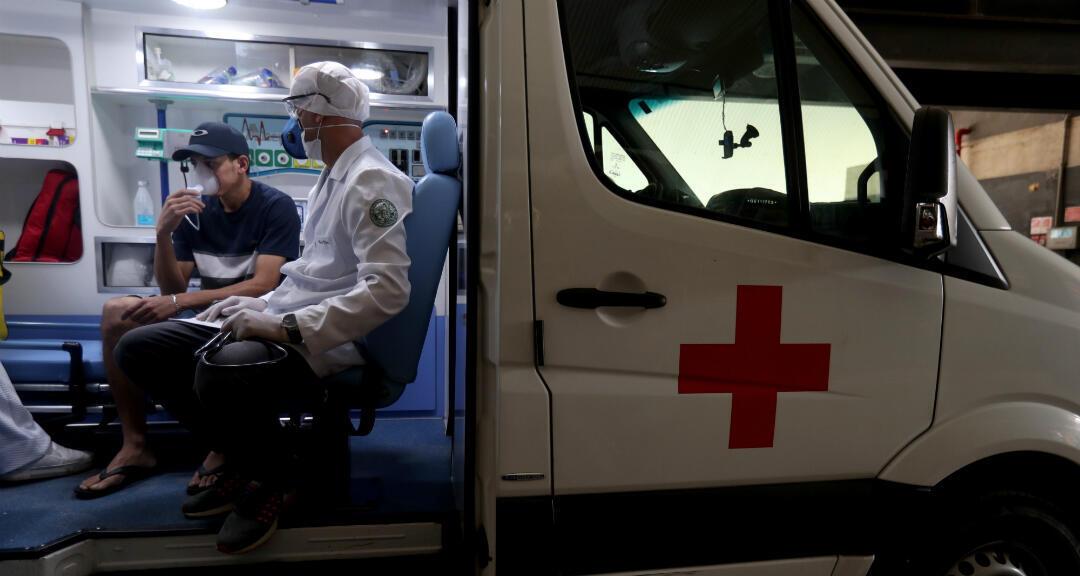 Imagen de archivo: personal médico junto a un paciente que utiliza un respirador dentro de una ambulancia en Brasil.