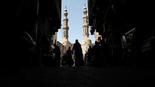 People shop on roofed Khayamiya Street in the old city of the Egyptian capital Cairo; A young Egyptian filmmaker imprisoned for directing a music video critical of President Abdel Fattah al-Sisi has died in a Cairo jail