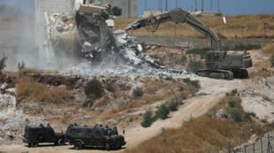Maquinaria militar israelí demuele un edificio palestino en la aldea de Sur Baher que se encuentra a ambos lados de la barrera israelí en Jerusalén Este y en la Cisjordania ocupada por Israel el 22 de julio de 2019.
