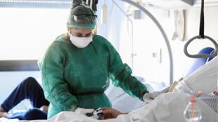 Une soignante examine un patient de l'unité de soins intensifs de l'hôpital d'Oglio Po, à Crémone, en Italie, le 19 mars 2020.
