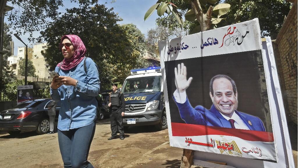 Une jeune égyptienne passe devant une affiche électorale montrant le président-candidat Abdel Fattah al-Sissi au Caire, le 26 mars 2018.