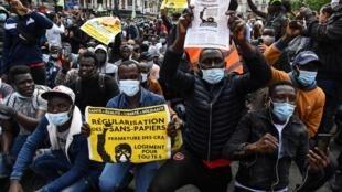 Des manifestants brandissent des pancartes pour la régularisation des sans-papiers lors d'une manifestation à Paris, le 20 juin 2020.