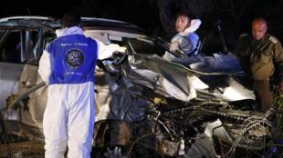 Las fuerzas de seguridad y forenses israelíes inspeccionan el vehículo destruido que fue utilizado por un asaltante palestino en un ataque de embestida de un auto contra un grupo de soldados israelíes cerca de Mevo Dotan en el norte de la Cisjordania ocupada el 16 de marzo de 2018. (Foto de AFP)
