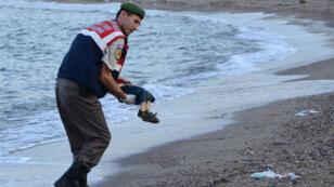 Un officier de police turc porte le corps sans vie d'une enfant syrien de trois ans, échoué sur une plage de Bodrum, dans le sud de la Turquie, le 2 septembre 2015.