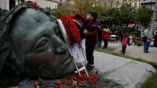 Un niño deja flores en el monumento dentro del Politécnico de Atenas, el 17 de noviembre de 2018, para conmemorar el 45 aniversario del levantamiento estudiantil de 1973, contra la junta militar que gobernaba el país en ese momento en Grecia.