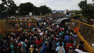 La caravana, que se dirige hacia EE. UU., cruzó el primer cerco policial para dirigirse a la reja que separa a Guatemala de México. 19 de octubre de 2018.