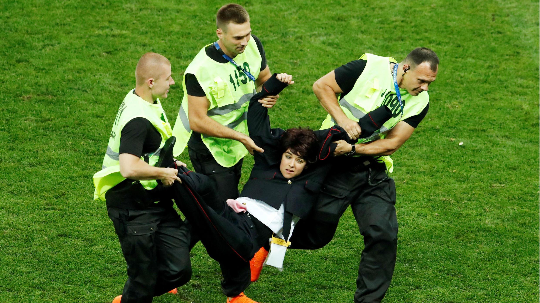 Los comisarios detienen a un invasor de campo en el estadio Luzhniki, Moscú, Rusia, el 15 de julio de 2018.