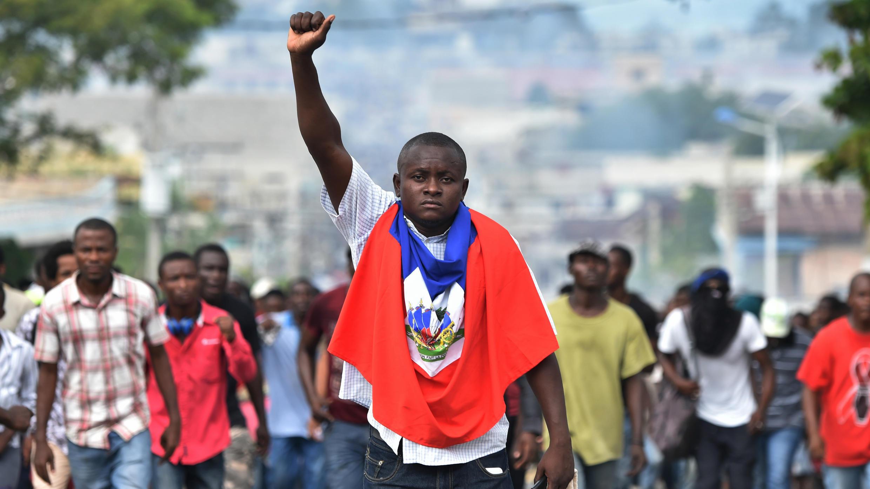 Un hombre levanta el puño durante una marcha por las calles de Puerto Príncipe, el 23 de noviembre de 2018, exigiendo la renuncia del presidente haitiano, Jovenel Moise.