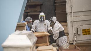Trabajadores de una funeraria trasladan un ataúd con el cuerpo de una víctima de covid-19 en el crematorio El Angel, en Lima, el 21 de mayo de 2020