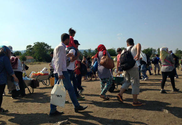 Migrants walk the last stretch towards the Serbian border. The wheelbarrows are filled with drinks for sale. (Photo: Fernande van Tets)