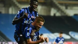 Le milieu croate de l'Atalanta Mario Pasalic (d) félicité par son coéquipier gambien Ebrima Colley après un but marqué contre Brescia, le 14 juillet 2020 à Bergame