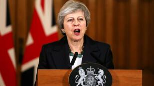 El escritorio de un gerente de inversiones, en la oficina de Aberdeen Standard Investments, se ve debajo de una televisión que muestra a la Primera Ministra de Gran Bretaña, Theresa May, entregando un comunicado a la Cámara de los Comunes, en Londres, Reino Unido, el 15 de noviembre de 2018.