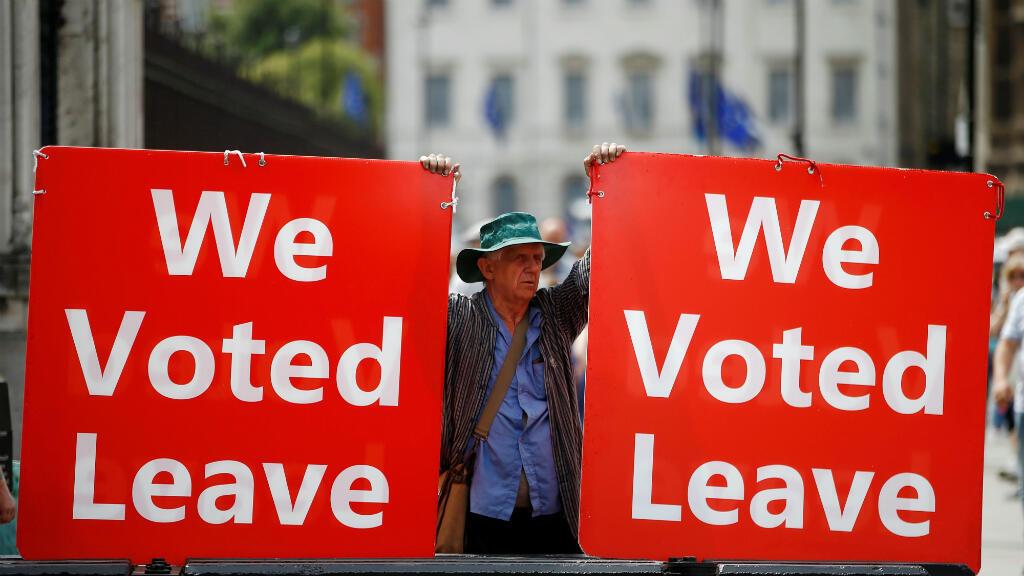 """Un manifestante a favor de Brexit sostiene pancartas con el mensaje """"Votamos salir"""" a las afueras del Parlamento británico, en Londres, Reino Unido, el 17 de julio de 2019."""