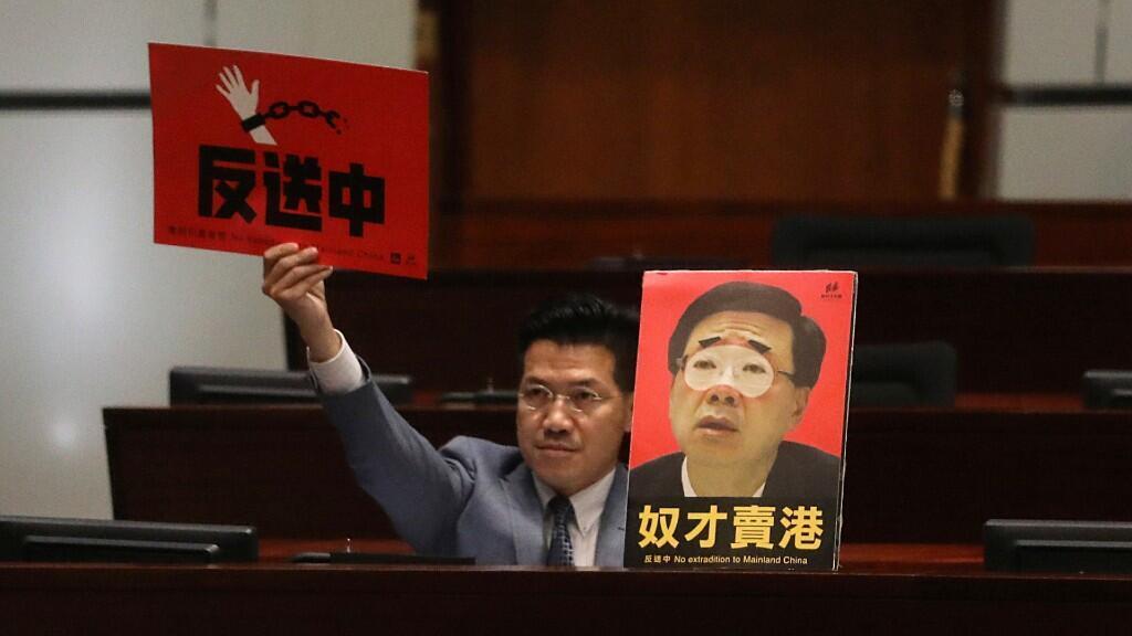 El legislador prodemocrático Gary Fan muestra carteles de ley contra la extradición mientras el Secretario de Seguridad John Lee Ka-Chiu anuncia la retirada del proyecto de ley de extradición, en Hong Kong, China, el 23 de octubre de 2019.