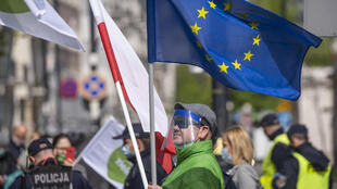 Protesters hold up the European and Polish flags during a demonstration in front of the parliament in Warsaw on May 7, 2020.