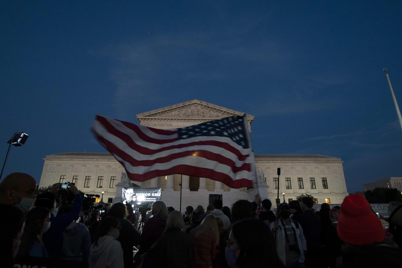 Una bandera estadounidense ondea frente a la Corte Suprema de Justicia, mientras las multitudes se reúnen para presentar sus respetos a la fallecida juez Ruth Bader Ginsburg, en Washington, Estados Unidos, el 19 de septiembre de 2020.