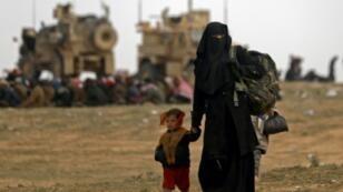 """امرأة وطفلها من بين مدنيين يفرون من المنطقة التي يسيطر عليها تنظيم """"الدولة الإسلامية"""" في بلدة الباغوز في محافظة دير الزوير في شرق سوريا في 13 شباط/فبراير 2019"""
