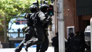Des dizaines de policiers armés encerlaient le Lindt Chocolate Cafe où se déroulait la prise d'otages lundi.