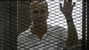 Australian Al-Jazeera journalist Peter Greste listens to the verdict in Cairo on June 23, 2014 inside the defendants cage during his trial for allegedly supporting the Muslim Brotherhood