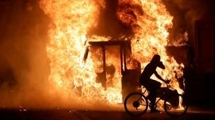 A man on a bike rides past a city truck on fire outside the Kenosha County Courthouse in Kenosha, Wisconsin, USA, during protests following the police shooting of Black man Jacob Blake on August 23, 2020.