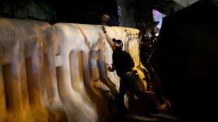 Un manifestant lance un projectile devant le batiment du conseil legislatif de Hong Kong, en Chine le 28 septembre 2019.