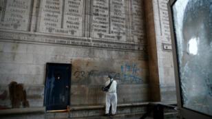 Des nettoyeurs enlèvent les graffitis sur l'Arc de triomphe à Paris, le 2 décembre 2018.