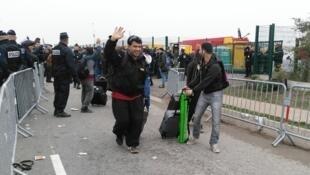 """Des migrants afghans convergeant vers les cars affretés par les autorités françaises pour évacuer la """"jungle"""" de Calais."""