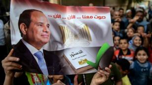 """El 22 de abril de 2019, un hombre egipcio sostiene una pancarta que dice: """"Vote con nosotros ... ahora"""" en una escuela en la aldea de Shamma, en la provincia de Menoufia, en Egipto."""