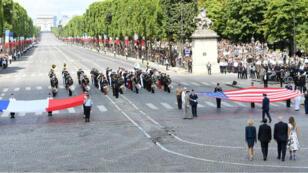 Les présidents français et américain, accompagnés de leurs épouses, devant les drapeaux sur les Champs-Élysées, le 14 juillet 2017.