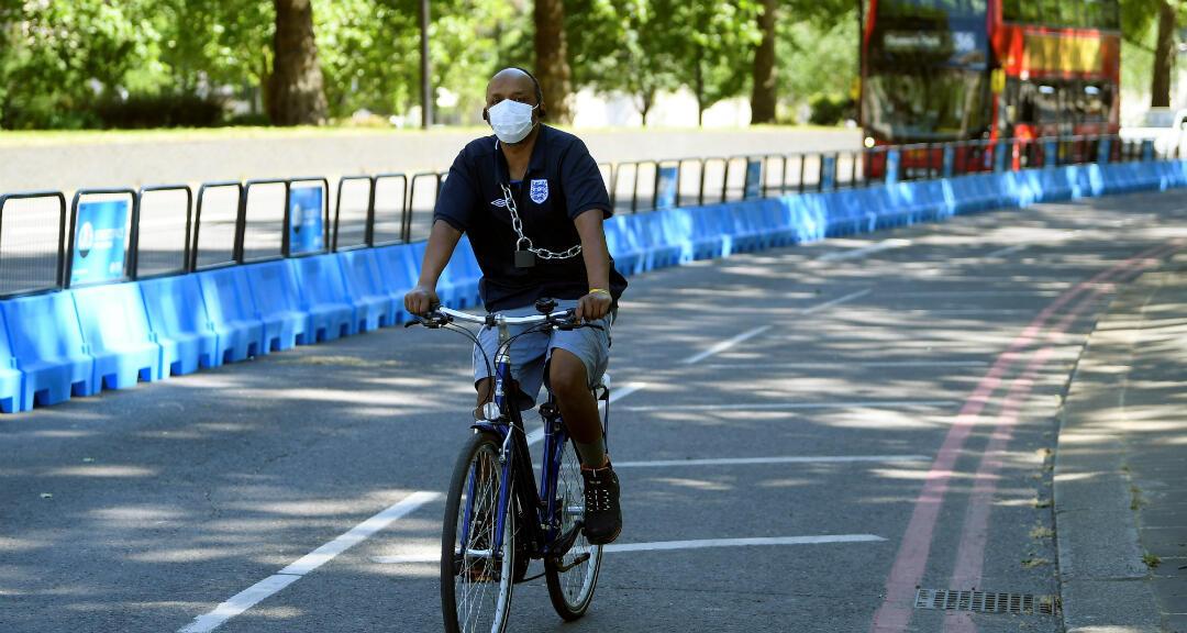 Un ciclista con una mascarilla se transporta por un carril para bicicletas creado en medio de la pandemia por coronavirus para evitar el contagio en el transporte público. Londres, Reino Unido, el 21 de mayo de 2020.