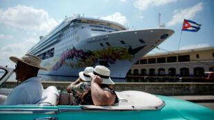 Unos turistas pasan en uno de los característicos coches cubanos frente a un crucero en La Habana, Cuba, el 7 de mayo de 2019