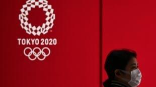 امرأة تضع كمامة لدى مرورها أمام شعار الألعاب الأولمبية في طوكيو في 24 آذار/مارس 2020