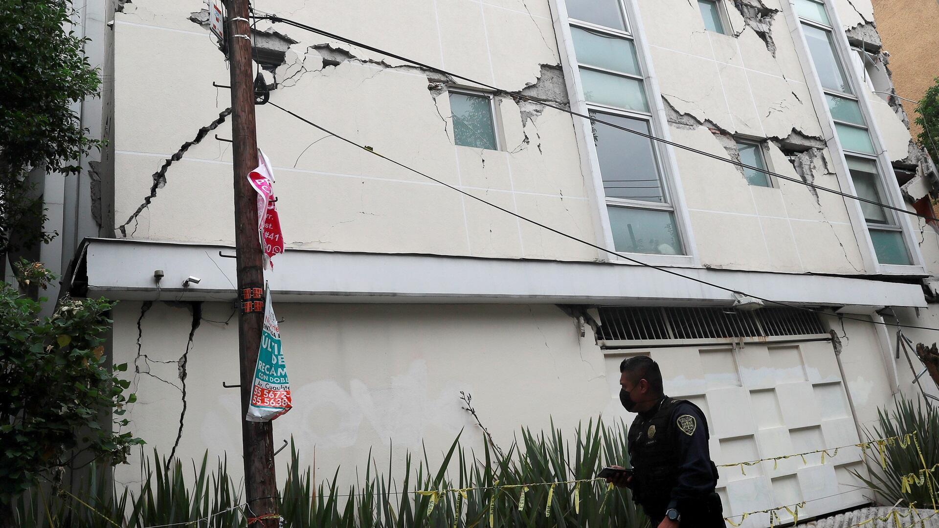 شرطي يتفحص تشققات في مبنى تضرر بفعل زلزال في العاصمة المكسيكية، 23 يونيو/حزيران 2020.