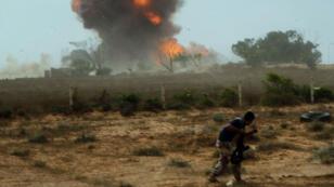Un membre des forces loyalistes au gouvernement d'union libyen, fuyant une explosion, à l'ouest de Syrte, le 2 juin 2016.