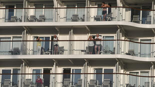 Passangers look out from their balconies aboard the Maltese-flagged  Mein Schiff 6, operated by German travel giant TUI, at the port of Piraeus