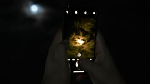 Un Indien prend en photo la Lune avec son smartphone.