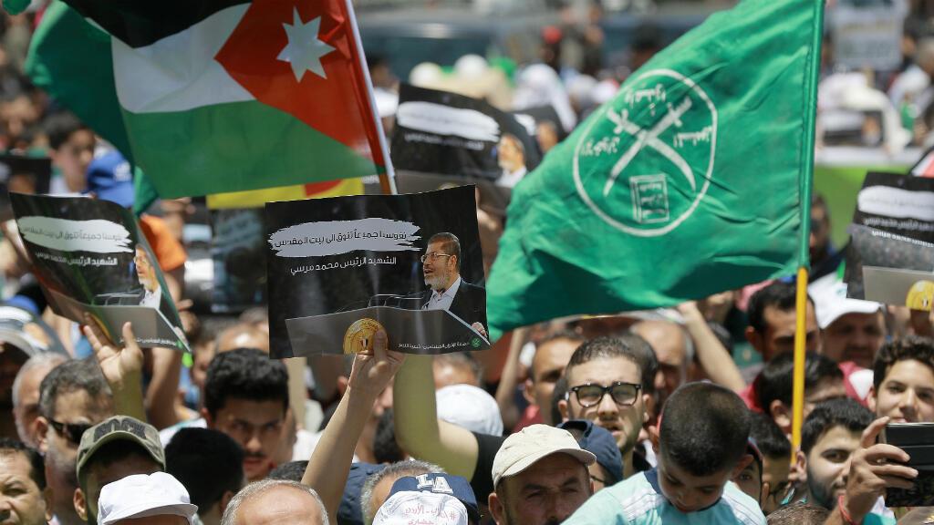 """Manifestantes agitan las banderas de Jordania y de los Hermanos Musulmanes junto a un cartel que muestra al derrocado presidente egipcio Mohamed Morsi, con leyendas en árabe que dicen """"El mártir Mohamed Morsi"""". Ammán, el 21 de junio de 2019."""