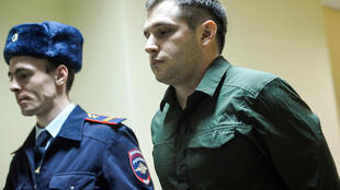 Police officers escort US ex-marine Trevor Reed, charged with attacking police, into a courtroom prior to a hearing in Moscow on March 11, 2020