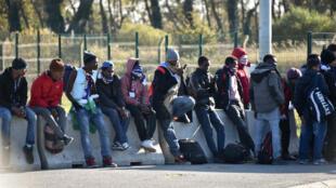 De jeunes migrants attendent un bus qui doit les emmener vers un centre d'accueil et d'orientation (CAO) le 28 octobre 2016 à Calais.